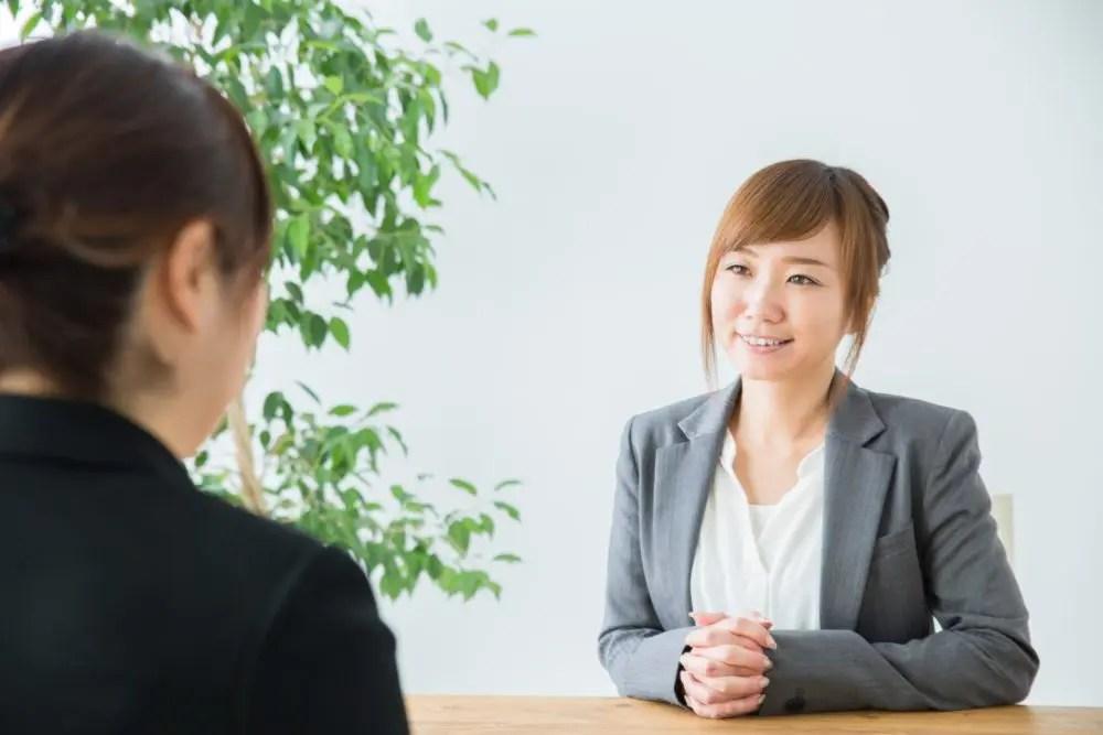銀行の窓口で金融商品の案内をするサービス技能士の資格を持つ女性