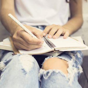 Девушка пишет в личном дневнике