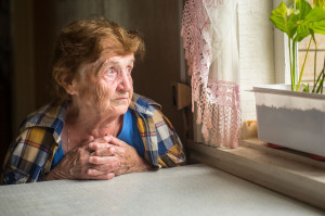 Old lonely woman sitting near the window in his house.