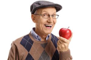 Cheerful senior having an apple