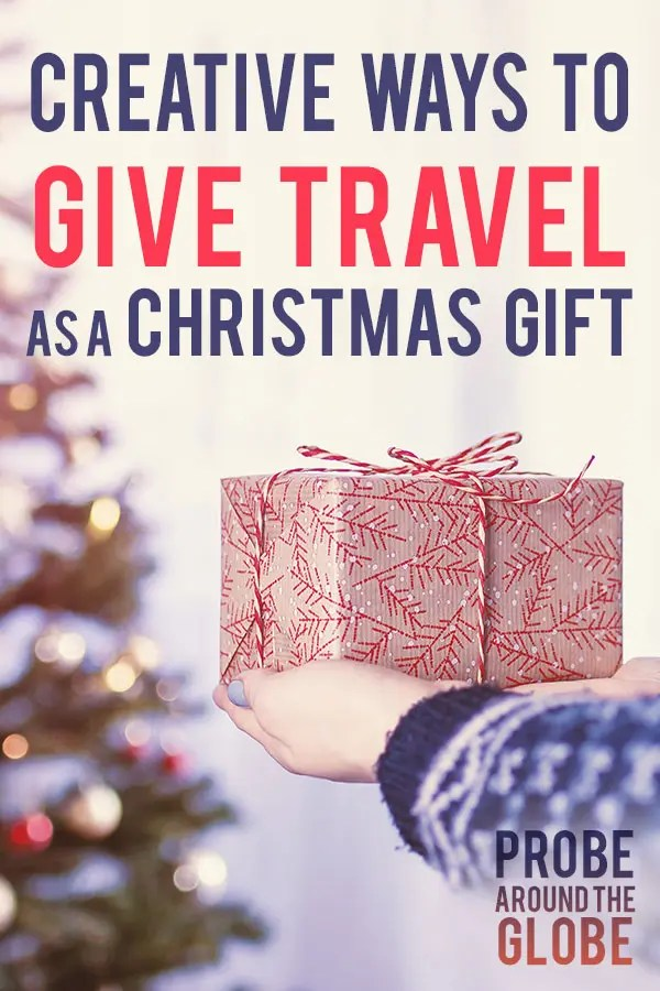 Gold Christmas present with ribbon against a bokeh Christmas background with text overlay saying: How to give Travel as a Christmas Gift. Probe around the Globe.
