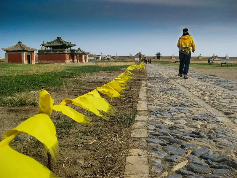 Women in yellow jacket walking on a cobble stone paved path away from the camera with yellow Buddhist prayer flags leading into the distance with temples and monasteries in the back against a bright blue sky.