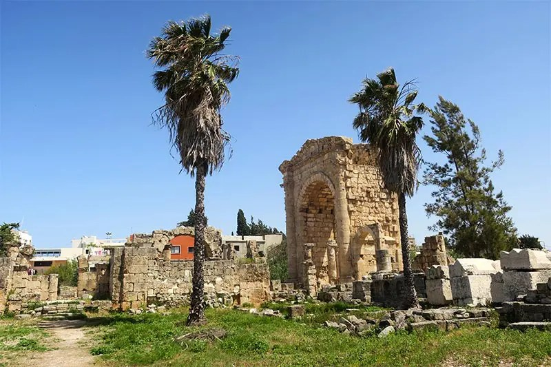 Palm trees, ancient Roman ruins and a triumphal gate at the Roman Ruins in Tyre that you can see on a day trip from Beirut Lebanon