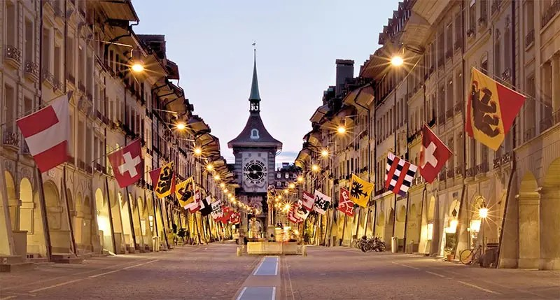 Kramgasse in Bern with flags and lighting. Make sure you visit Bern, one of the most beautiful places in Switzerland.