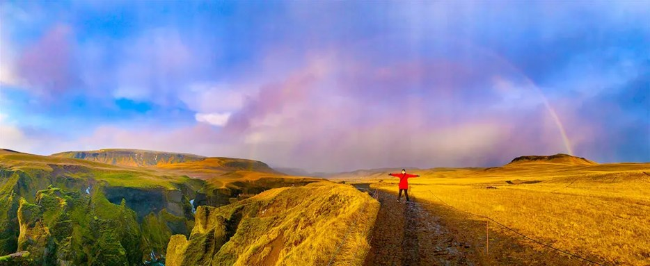 Woman in red winter coat standing underneath a rainbow surrounded by green landscape and fields.