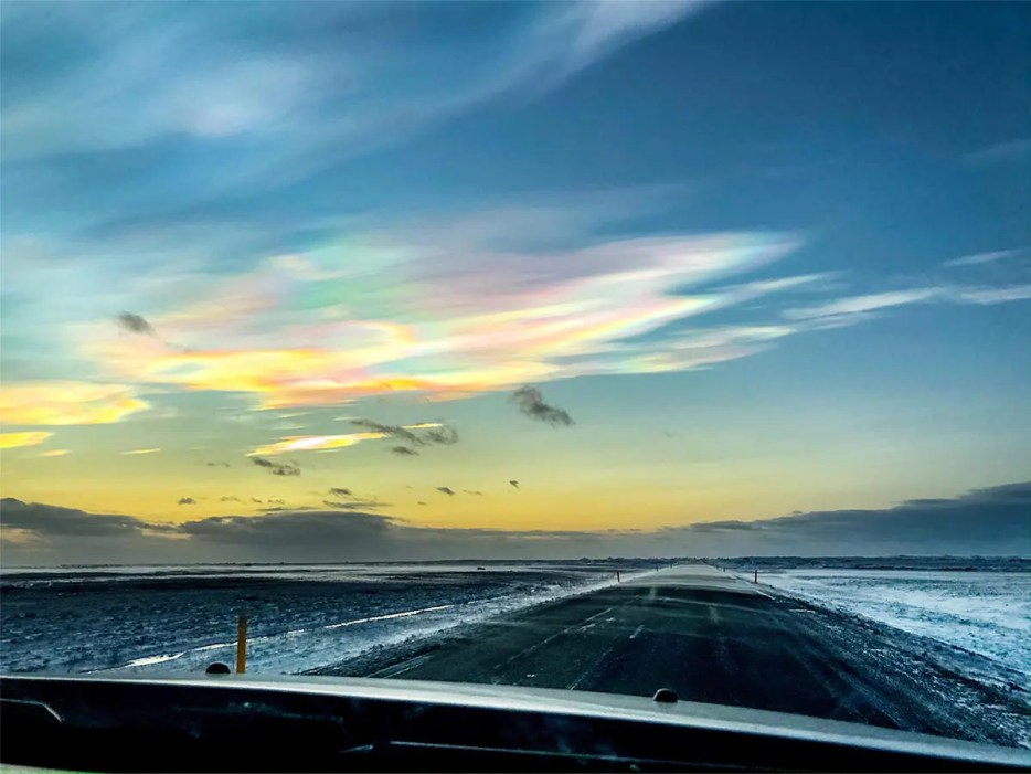 View from a car window on asphalt road with snow on the sides. A pale blue sky with circular clouds in all the colors of the rainbow.