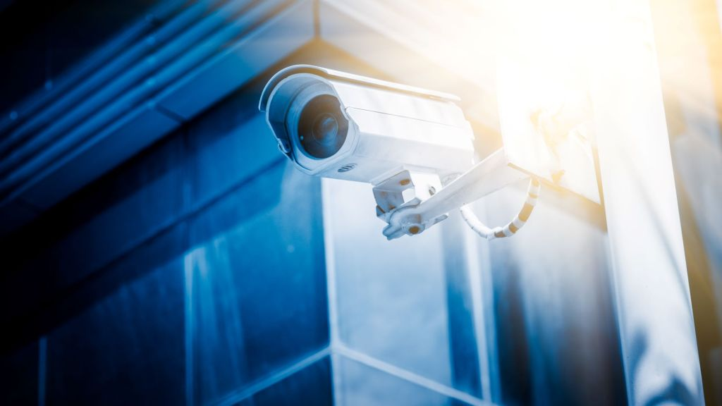 A surveillance camera bathed in blue light points off camera toward the left.
