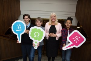 Photo of Mary Mitchell O'Connor with young students holding speech bubbles with colourful language icons