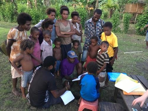 Porer Nombo explaining the TKRN books and method to Tokain villagers