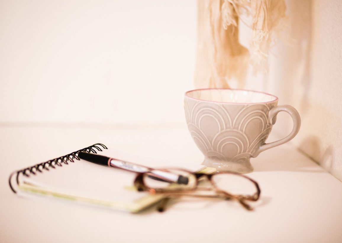 Pad of paper, pen, glasses and a coffee cup on a flat surface