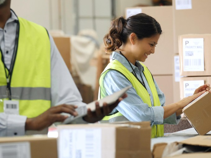 Confident male and female distribution warehouse workers prepare to send out packages to customers. A female employee is placing a mailing label on the package. A male employee is using a digital table tin the foreground.