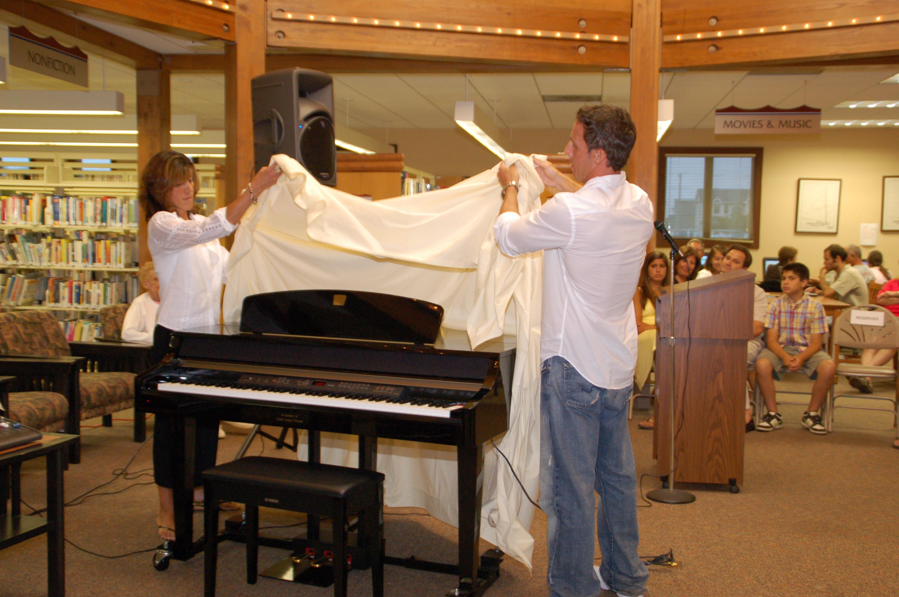 Angela Fioretti and Mike Vizzone unveil the piano donated in Linda Vizzone's memory.