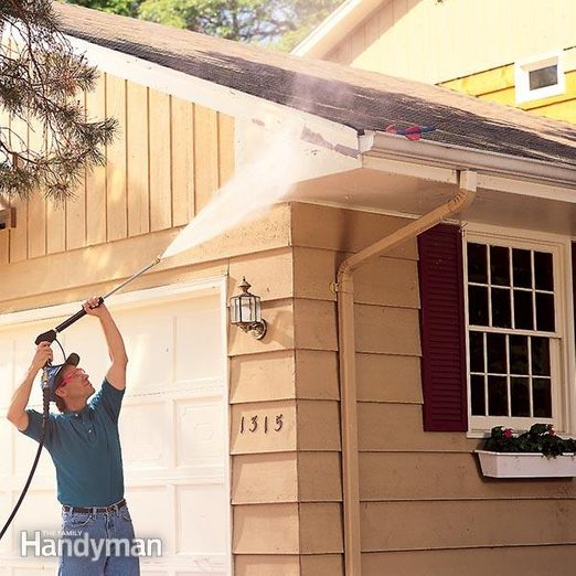 man pressure washing house for painting