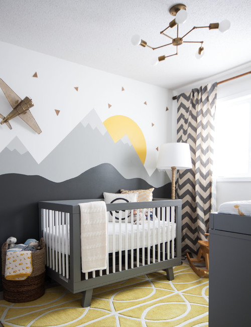 baby's nursery with crib and mountains painted on wall