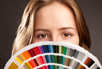color consultant holding paint clips fanned out in front of face