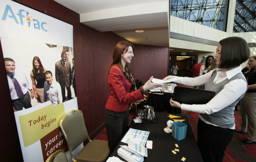 Alison Smith, right, of Coupeville, Wash., hands a resume to Andrea Phaneuf, a special projects coordinator with the Aflac Inc. insurance company, as Smith attends an employment event hosted by National Career Fairs, Monday, March 2, 2009, in Bellevue, Wash. Smith, who has a degree in business administration, recently moved to Washington from New York and was attending her first job fair. (AP Photo/Ted S. Warren)