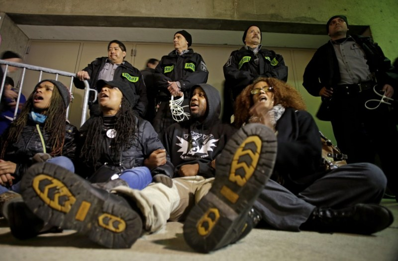 Protesters yell outside the Bradley Center before an NBA basketball game between the Milwaukee Bucks and the Charlotte Hornets Tuesday, Dec. 23, 2014, in Milwaukee. The group is protesting Monday's announcement  that no charges against former police office Christopher Manney were filed in the fatal shooting of Dontre Hamilton. (AP Photo/Morry Gash)