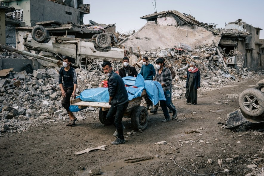MOSUL, IRAQ, MARCH 24: Local volunteers carry the bodies of civilians found in the rubble of a building in the Mosul al Jadidah neighborhood of Mosul.
