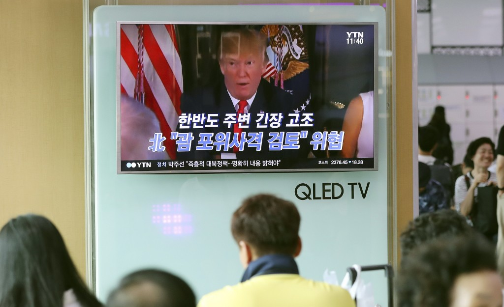 "People watch a TV screen showing a local news program with an image of U.S. President Donald Trump, at Seoul Train Station in Seoul, South Korea, Wednesday, Aug. 9, 2017. North Korea and the United States traded escalating threats, with President Donald Trump threatening Pyongyang ""with fire and fury like the world has never seen"" and the North's military claiming Wednesday it was examining its plans for attacking Guam. The letters read ""North Korea, Examine, the enveloping fire at Guam."" (AP Photo/Lee Jin-man)"