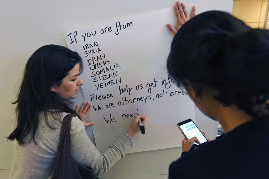 Members of a coalition of immigration lawyers wait for people affected by US President Donald Trump's temporary ban on incoming refugees and travelers from seven Muslim countries, at the Los Angeles International Airport, California on January 30, 2017.Trump's executive order suspended the arrival of all refugees for at least 120 days, Syrian refugees indefinitely -- and bars citizens from Iran, Iraq, Libya, Somalia, Sudan, Syria and Yemen for 90 days. Protests are taking place at airports across the country in opposition to the ban. / AFP / Mark RALSTON (Photo credit should read MARK RALSTON/AFP/Getty Images)