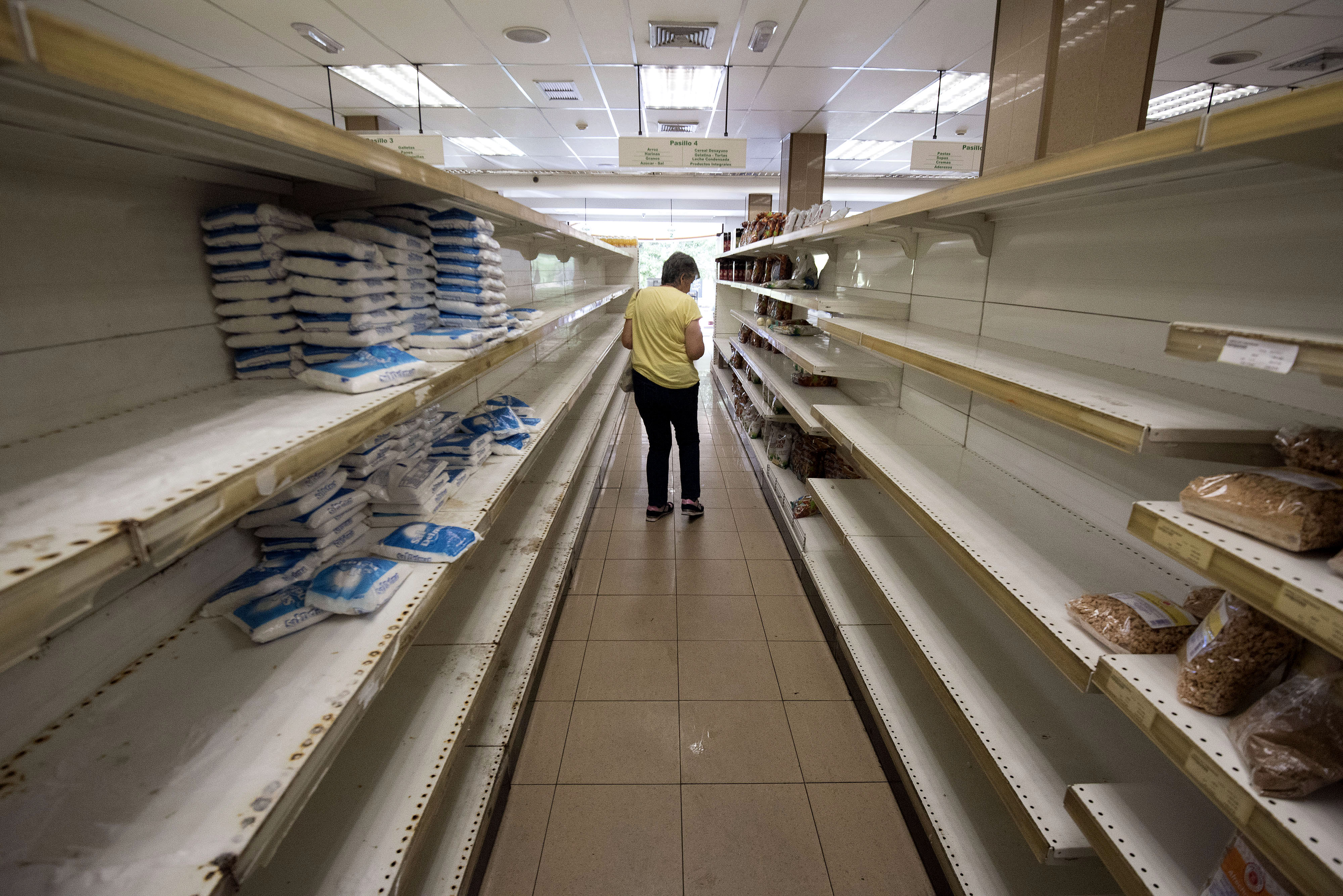 A customer shops for groceries at a supermarket in Caracas, Venezuela, on Tuesday, July 25, 2017. Venezuelans are stockpiling scarce food and water as tensions mount ahead of a widely criticized Sunday vote that President Nicolas Maduro has called to elect an assembly of supporters to rewrite the constitution and strengthen his grip on power. Photographer: Carlos Becerra/Bloomberg via Getty Images
