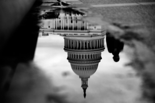 The U.S. Capitol is reflected in a puddle next to the Capitol Reflecting Pool in Washington, D.C., U.S., on Tuesday, Oct. 15, 2013. The House scrapped a vote tonight on a fiscal plan that contains almost none of Republicans' initial conditions for ending the 15 day-old government shutdown and raising the debt ceiling said Representative Pete Sessions, chairman of the House Rules Committee. Photographer: Andrew Harrer/Bloomberg via Getty Images