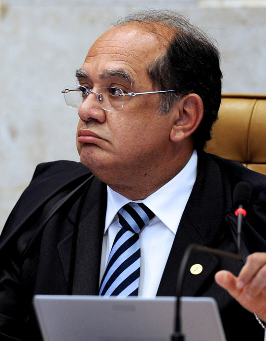 Brazilian Supreme Court President Gilmar Mendes speaks during the trial of Italian Cesare Battisti in Brasilia, on November 18, 2009. Brazil's Supreme Court is to resume on Wednesday its weighing of an extradition demand for an Italian ex-militant, with the outcome potentially creating a constitutional clash of powers. The court so far is evenly split on the case of whether to send Cesare Battisti, 54, back to Italy to serve a life sentence for murders committed in the 1970s. A vote by chief justice Gilmar Mendes is to break a 4-4 deadlock among his colleagues. The placards read