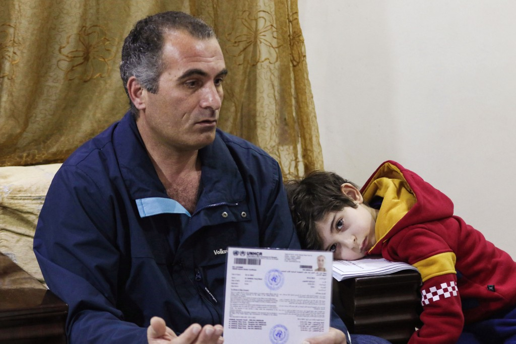Faraj Ghazi al-Jamous, a Syrian refugee who was prevented from travel to the United States due to President Donald Trump's executive order blocking entry to citizens from seven Muslim-majority countries, including Syria, sits in a living room with his son, showing documents provided by the UNHCR verifying his status, in the Jordanian capital Amman on February 1, 2017. After spending over a year amid interviews, health and security checks, Jamous, a father of five who was travelling with his wife and children, was contacted by a representative from the International Organisation of Migration (IOM) who told him that the family's immigration and resettlement plans were suspended indefinitely. / AFP / Khalil MAZRAAWI        (Photo credit should read KHALIL MAZRAAWI/AFP/Getty Images)