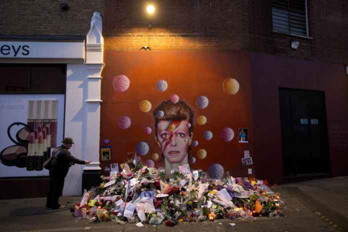 A man takes a picture of tributes laid beside a mural of British singer David Bowie by artist Jimmy C in Brixton, south London, Tuesday, Jan. 12, 2016. Bowie, the other-worldly musician who broke pop and rock boundaries with his creative musicianship, nonconformity, striking visuals and a genre-spanning persona he christened Ziggy Stardust, died of cancer Sunday aged 69. He was born in Brixton. (AP Photo/Matt Dunham)