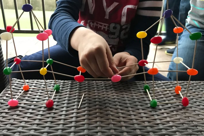 child's hand making a jelly bean toothpick building