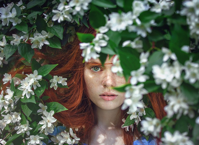 Woman peering from within a bush