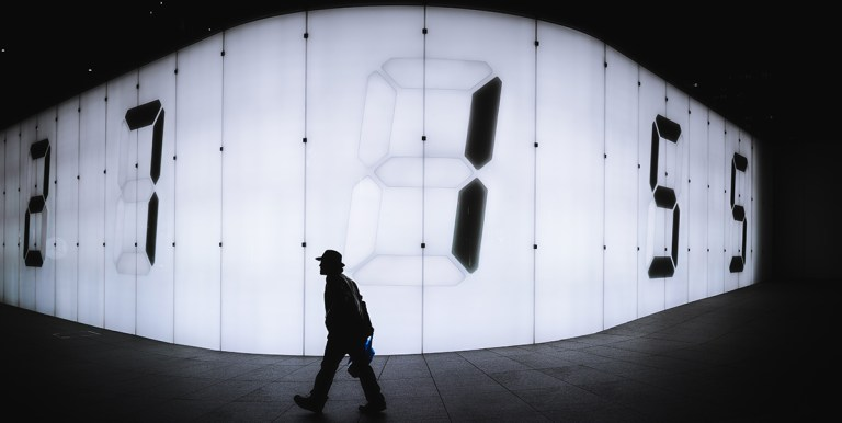Man walking in front of an illuminated wall with large modern numbers
