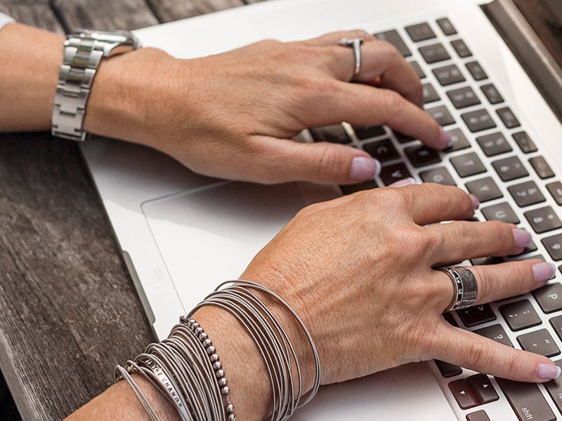 Older woman's hands typing on a laptop