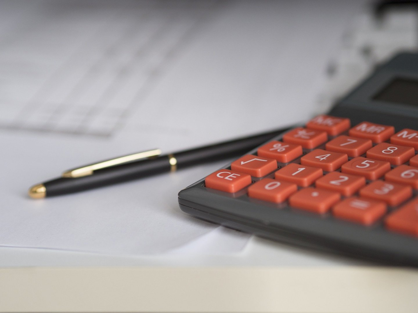 calculator and pen sitting on a financial document