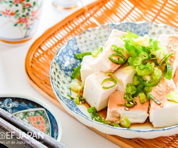 Foto van koude tofu (hiyayakko) met lenteui, sesamzaadjes, en sojasaus.