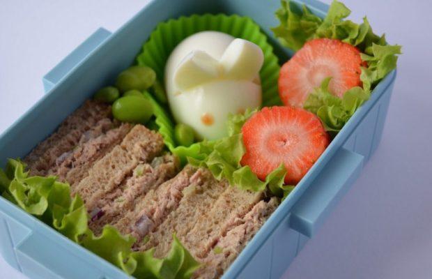 Bento box met bruine boterham en tonijnsalade, en een gekookt eitje gevormd tot een konijntje.