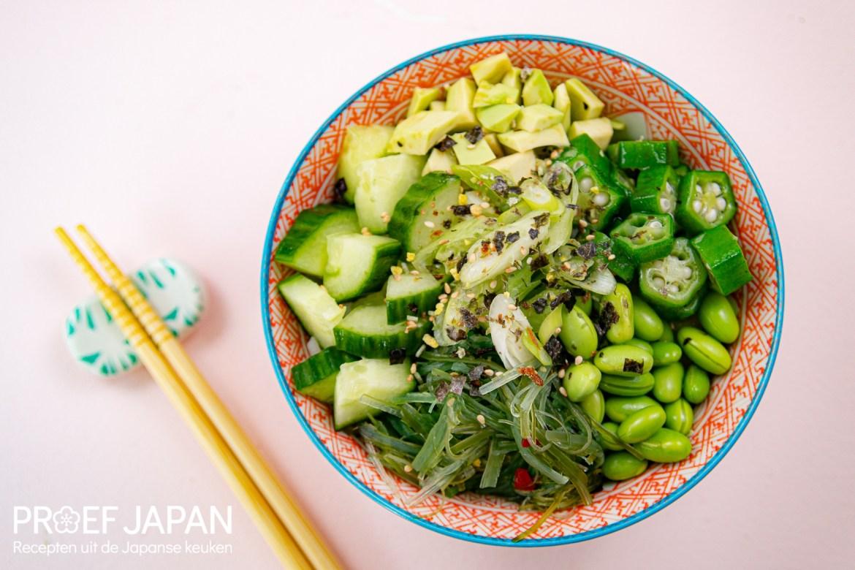 Foto van een groene Buddha bowl. Met ingrediënten zoals komkommer, avocado, okra, edamame bonen, zeewier, bosui, wasabi furikake. Met daaronder rijst.