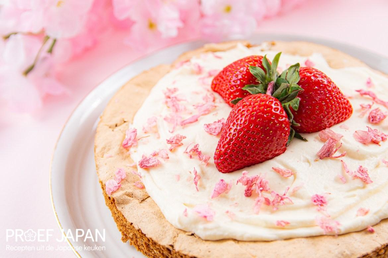 Proef Japan foto van een merengue taart met kersenbloesemslagroom en een aardbei.