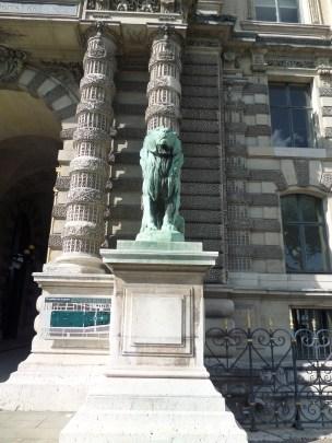 Lion stands guard outside Porte des Lions entrance along the Seine side.