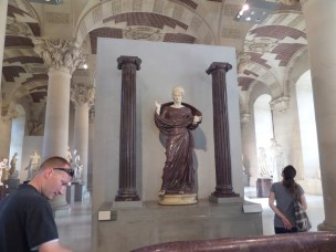 Statue of woman, 2nd century AD, Roman, porphyry. In the background one can see the beauty surroundings of the Salle du Manege.