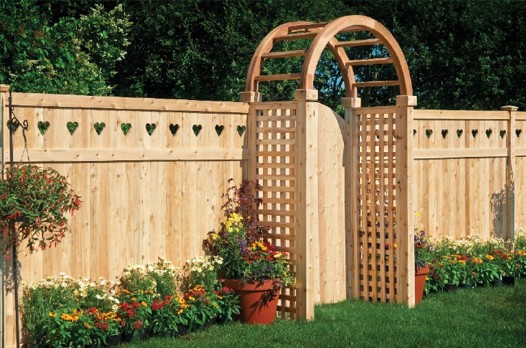 Eastern White Cedar one piece T&G Cedar privacy panels with Heart cutout shown with an arbor, square lattice side panesl and a style 20 gate