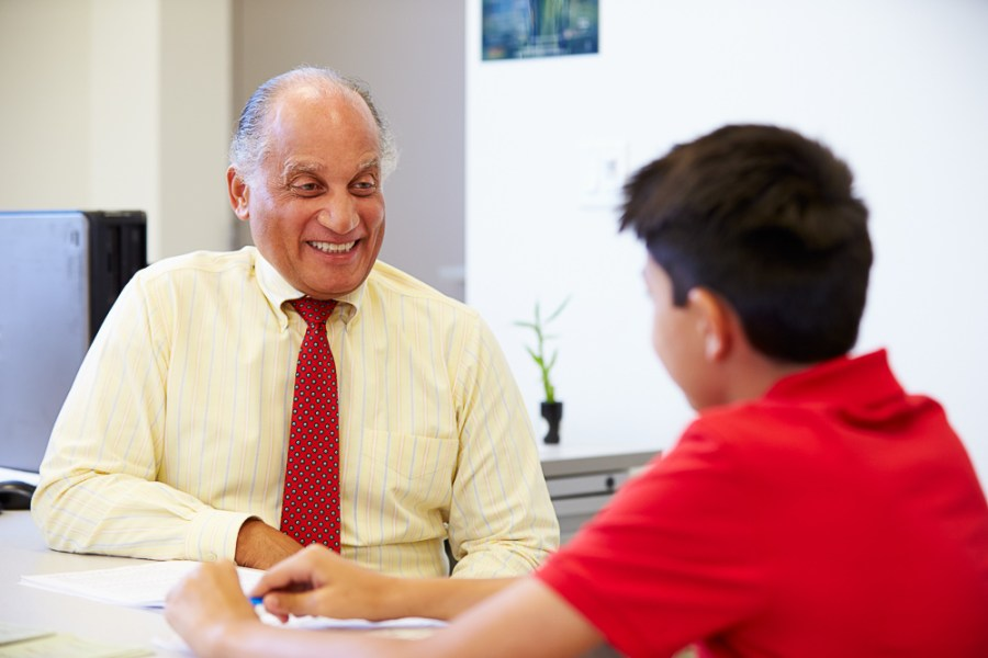 Latino student and male teacher talking