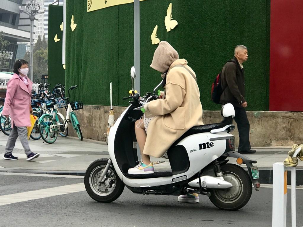 Joven china mirando las redes sociales en la moto