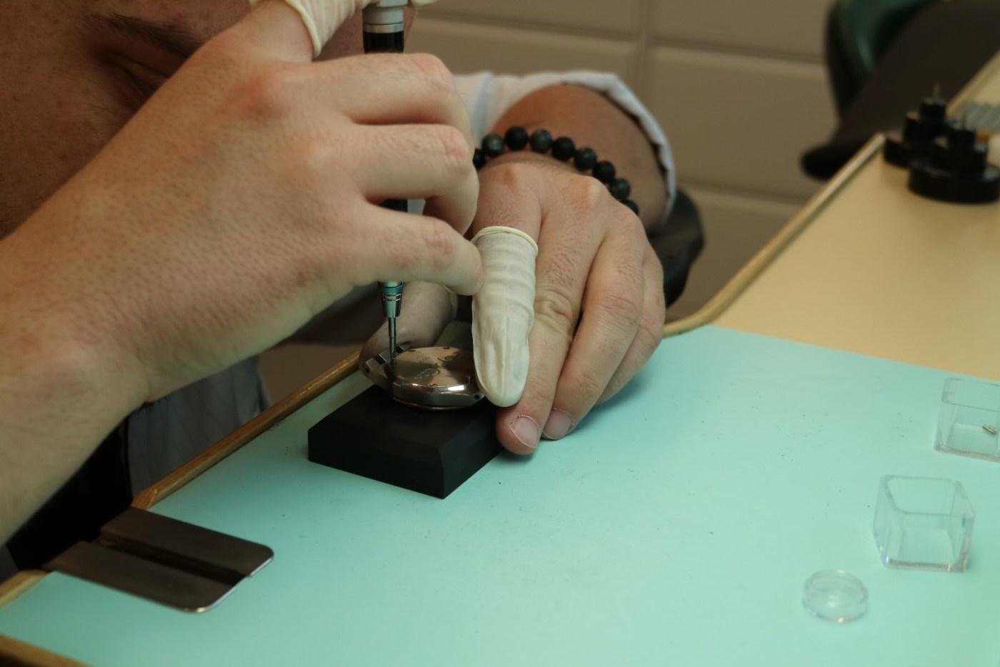Watchmaker removing case back screws