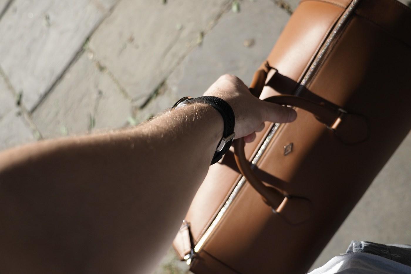 Cartier Two-Tone Diver's Watch wristshot holding Louis Cartier 24 Hour leather bag