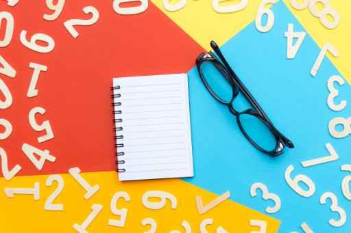 black framed eyeglasses beside notebook