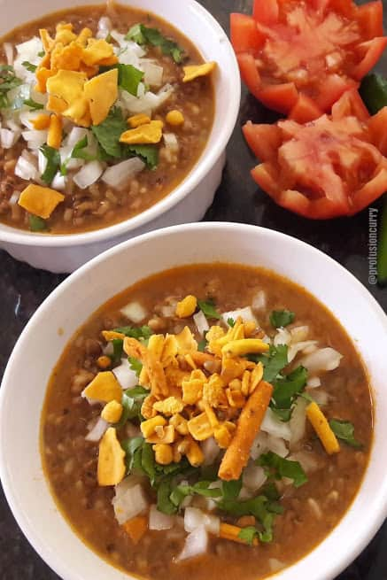 Marathi Misal curry served in two white bowls with cilantro, onion , sev topping and cut tomatoes on the side. This profusioncurry recipe is popular breakfast /brunch item of Indian street food chat.