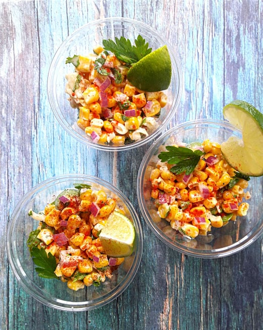 Mexican Corn Salad with corn, cheese, mayo and spices served in a cup with lemon wedges