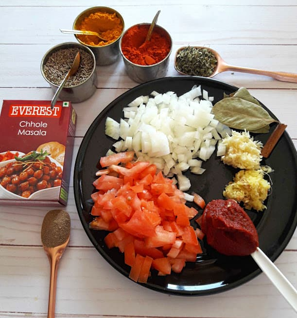 Chana Masala Ingredients and spices on black platter