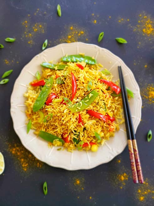 Golden turmeric hued Curry Fried rice served with colorful veggies on black background and chopsticks with lime wedges